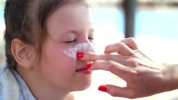 close-up, the child, girls, severe sunburn on the face. Mom smears places of burns abundantly with a special cream. Mother applying sun protection cream to her daughter face
