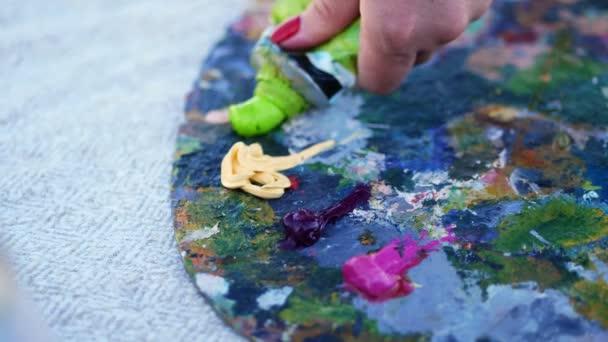 Nahaufnahme, Kunstpalette. drückt der Künstler etwas grüne Farbe aus einer Röhre. Es gibt einen kreativen Prozess. Künstler malt in der Natur