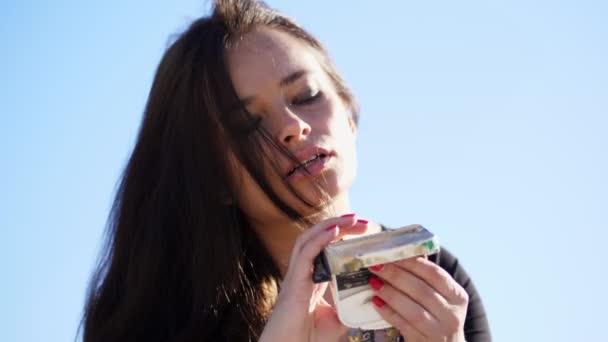 Eine schöne Künstlerin drückt mit einem speziellen Gerät, dem Lifhak, Farbe aus einer Tube. Es gibt einen kreativen Prozess. Künstler malt in der Natur. gegen den blauen Himmel
