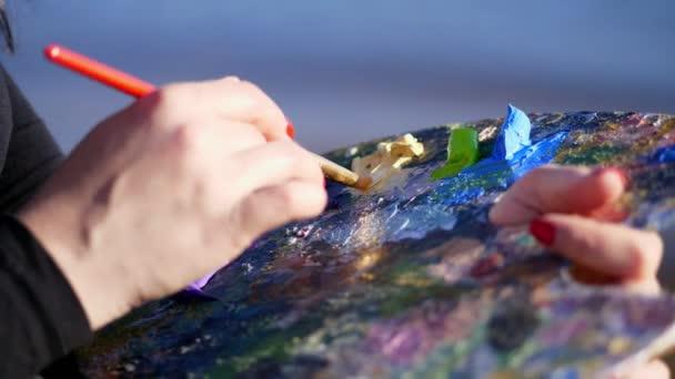 Sommer, im Freien, Nahaufnahme weiblicher Hände des Künstlers und eine Palette mit Farben, der Künstler mischt Farben mit einem Pinsel auf der Palette.