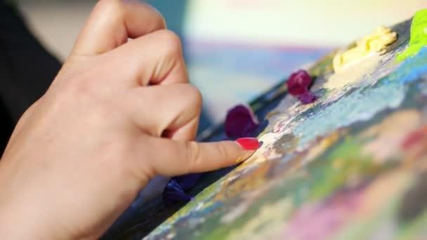 Sommer, im Freien, Nahaufnahme weiblicher Hände des Künstlers und eine Palette mit Farben, der Künstler mischt Farben mit den Fingern auf der Palette. Nasser Finger in der Farbe
