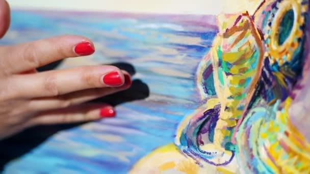 Nahaufnahme, weibliche Hände der Künstlerin mit leuchtend roter Maniküre. Mit den Fingern trägt sie Farbe auf die Leinwand auf, wobei sie eine spezielle Zeichentechnik anwendet. .