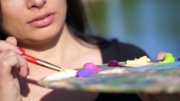 Sommer, im Freien, Nahaufnahme einer Palette mit Farben, die Künstlerin mischt Farben mit einem Pinsel auf der Palette.