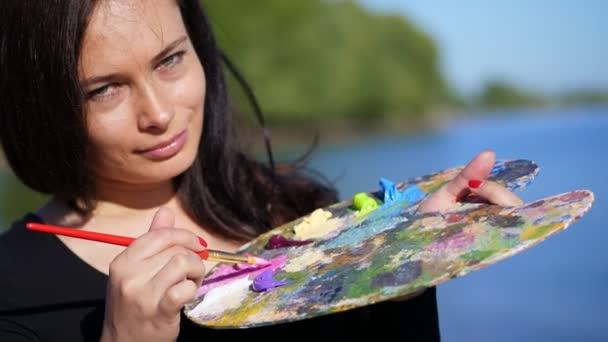 Sommer, im Freien, Porträt einer schönen vierzigjährigen brünetten Künstlerin, Nahaufnahme einer Palette mit Farben, die Künstlerin mischt Farben mit einem Pinsel auf der Palette.