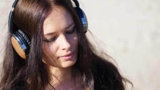 summer, against the background of the sea. beautiful woman, with long dark hair, listening to music on headphones from a mobile phone, device, outdoors, dances. Enjoying Music