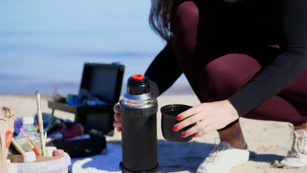 summer, sea beach. sunrise, woman artist in spare time from drawing, has snack, picnic, lunch, breakfast outdoors. close-up, womens hands pour tea from a thermos into the cup.