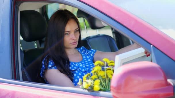 művész, gyönyörű barna nő ül az autóban, felhívja a ceruzarajz, rajz csokor sárga pitypang. nyári