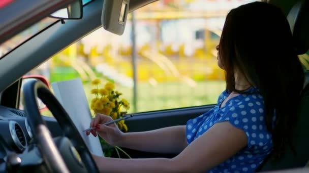 művész, gyönyörű barna nő ül az autóban, felhívja a ceruzarajz, rajz csokor sárga pitypang. a természet, a kreatív folyamatot, rajz rajz. nyári
