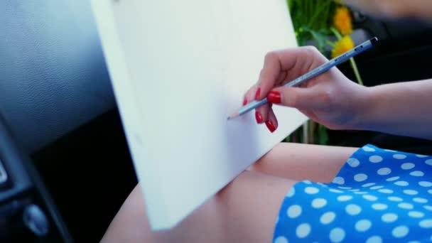 detail. na klíně kreslířce je plátno s tužkou kytice pampelišky. ona sedí v autě. kresba z přírody, tvůrčí proces kreslení