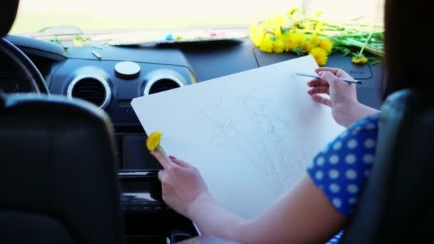 umělec, krásná bruneta žena, sedí v autě, kreslí tužkou, kresba kytice žlutých pampelišek. kresba z přírody, procesu tvorby výkresu. léto