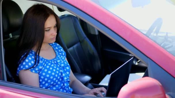 schöne brünette Frau im blauen Kleid, sitzt im Auto, arbeitet am Laptop und kommuniziert in sozialen Netzwerken. nutzt das Internet, mobile Kommunikation