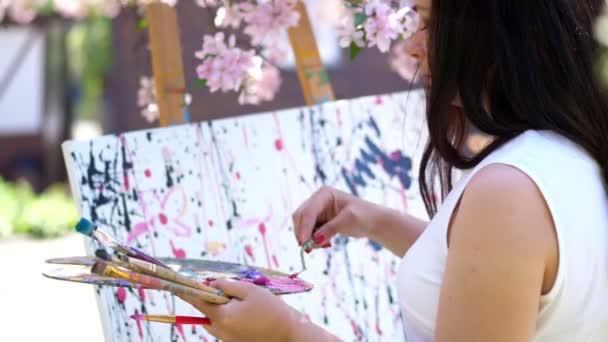 egy gyönyörű nő festő fehér ruha, virágzó tavaszán almaültetvényben, ő festékek keveredik különleges kis spatula a raklapon. művész fest egy képet a virágok
