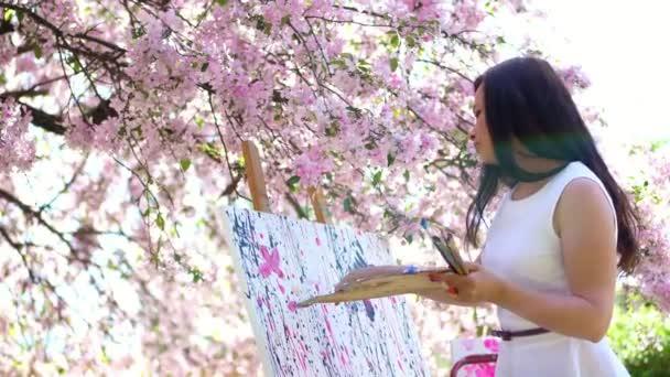 egy gyönyörű nő festő fehér ruhában, művész festékek, egy képet a virágzó virágok tavaszi almaültetvényben, ő vonatkozik festékek a vásznon egy különleges kis spatula segítségével különleges lehívási