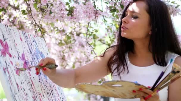 portréja egy gyönyörű nő festő fehér ruhában, művész festékek, egy képet a virágzó virágok tavaszi almaültetvényben, ő vonatkozik festékek a vásznon egy különleges kis spatula segítségével egy