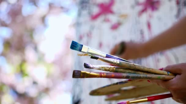 close-up, female hands, painter, artist paints a picture of flowers in blooming spring apple orchard, she holds palette with paints and brushes