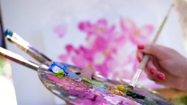 közeli, női kéz, festő művész fest egy képet a virágok, ő tartja a palettán, a festékek és ecsetek, mixek festékek ecsettel a raklapon