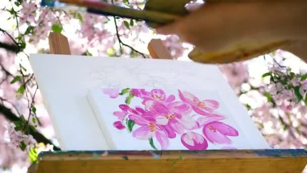 közeli, festő rajzolhatók, a virágok virágzó tavaszi almaültetvényben, ő festékek, ecset, tart palettán, a festékek. szél söpör virágzó ágak át a festőállvány
