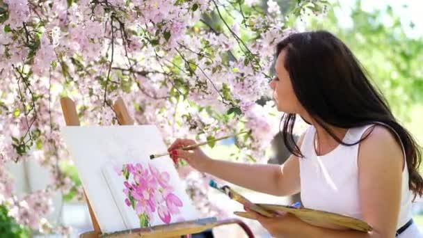 egy gyönyörű nő festő fehér ruhában, művész festékek, egy képet a virágzó virágok tavaszi almaültetvényben, ő tartja a paletta a festéket, egy ecsetet a kezét