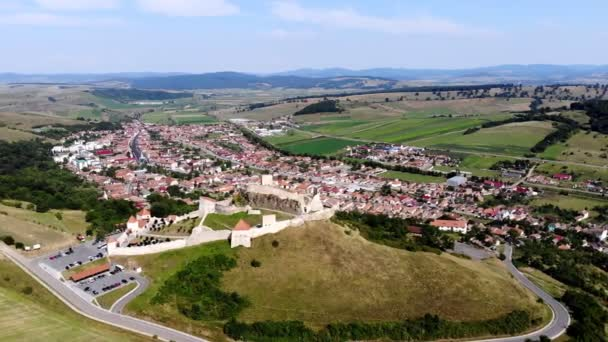 aero. panoramic view of the ancient castle, Rupea defense fortress placed on top of a hill. at the foot of castle there is a small town. Transylvania, Romania. sunny hot summer day