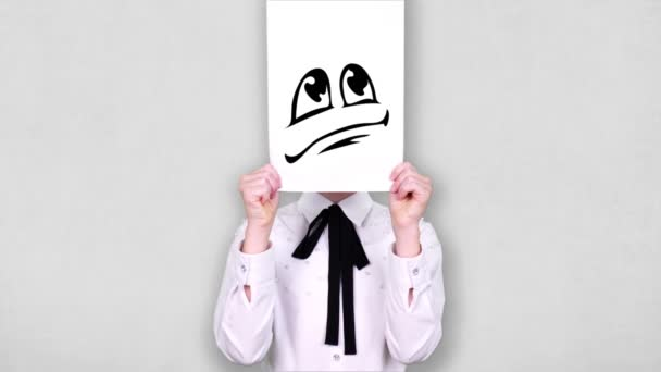 portrait, teenager holds white paper sheet with disappointed smiley drawing, animation, covering face. emotions, Imagination, creativity, successful idea concept.