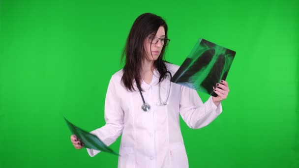 Portrait of female doctor in glasses, dressed in white medical uniform and with stethoscope, examines X-ray images of the patients lungs on green background.