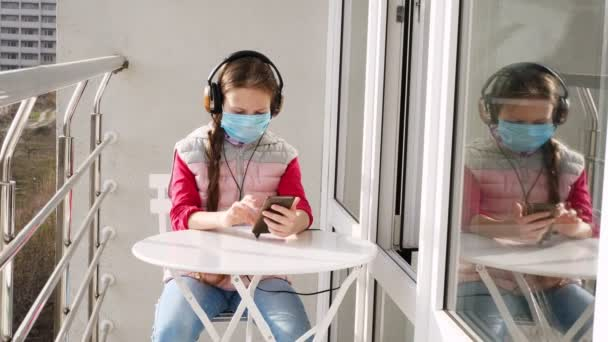 teenager girl in mask and headphones, uses a smartphone, makes selfie, on open balcony. spring sunny day. concept of quarantine, chat online. stay at home. coronavirus epidemic.