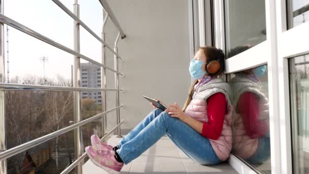 teenager girl in mask and headphones, listening to music on tablet, on open balcony. spring sunny day. quarantine. stay, study at home. coronavirus epidemic.