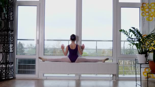 Young ballet dancer, teenage girl performing exercise twine , stretching her legs, sit in twine, against the background of a large panoramic window.