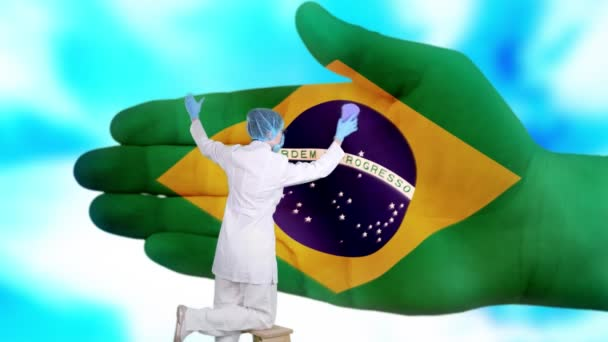 Nurse in medical mask and gloves washes large hand, painted in colors of Brazil flag. State care for nation health. Wash your hands concept. Viruses protection. Diseases prevention.