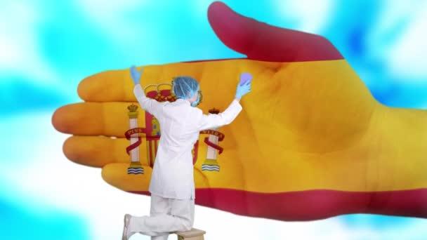 Krankenschwester mit medizinischer Maske und Handschuhen wäscht große Hand, bemalt in den Farben der spanischen Flagge. Der Staat sorgt für die Gesundheit der Nation. Waschen Sie sich die Hände. Virenschutz. Prävention von Krankheiten.