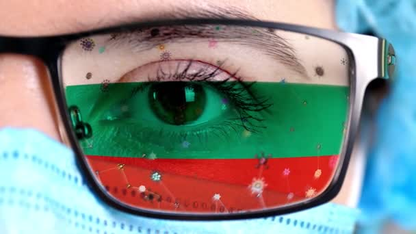 closeup, eye, part of doctor face in medical mask, glasses, which painted in colors of Bulgaria flag. Many viruses, germs moving on glass.State interests in vaccines, drugs invention, pathogenic