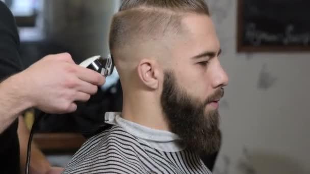 Vážný mladý vousatý muž dostává účes od profesionální kadeřnictví v holičství