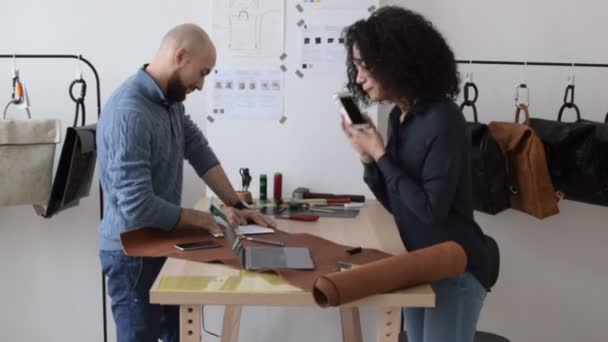 Two casual colleagues working together in small studio