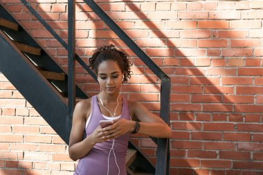 Woman browsing on her mobile, choosing music for workout
