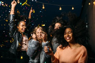 Group of female friends enjoying night party, throwing confetti