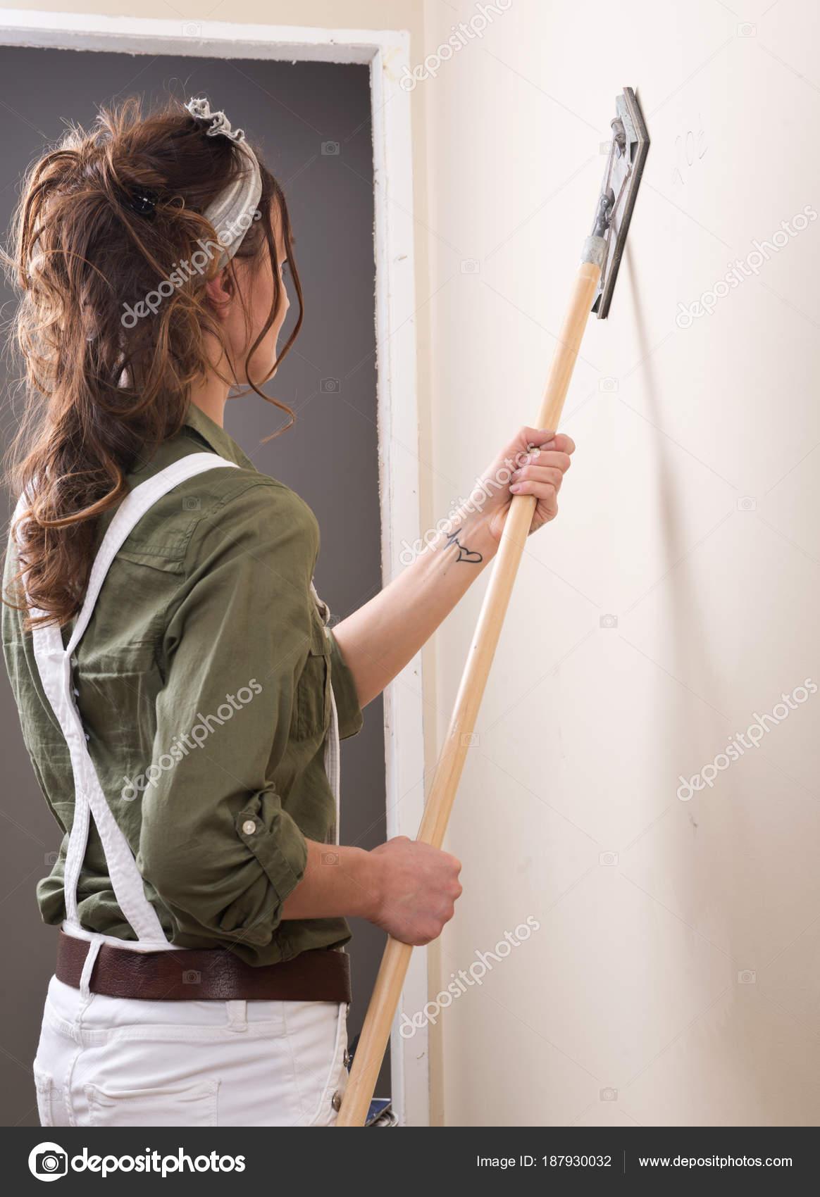 Jeune Femme Est Poncer Mur Avec Ponceuse De Poteau Avant De Peindre Dans La  Maison Sous Le Remodelageu2013 Images De Stock Libres De Droits
