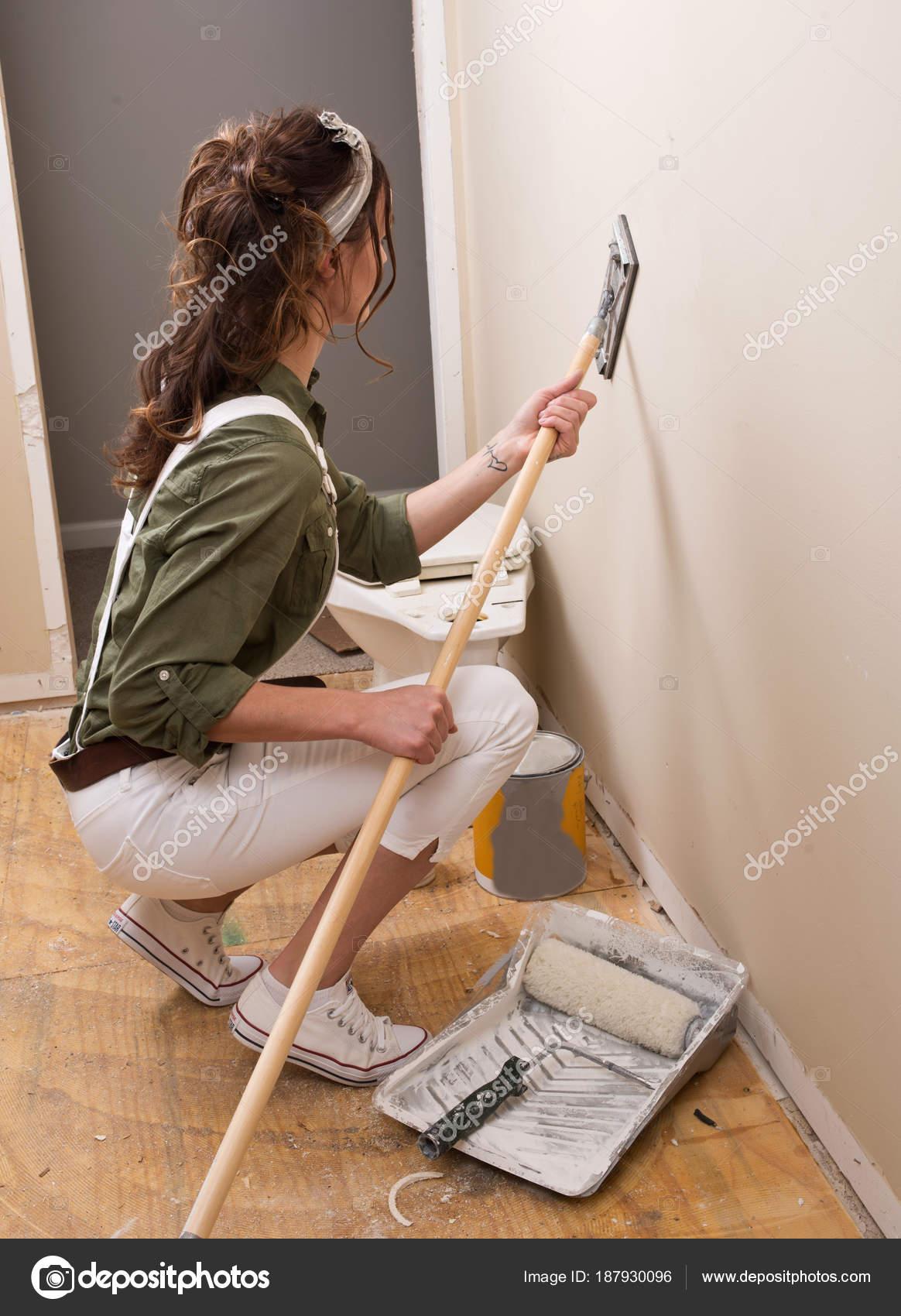 jeune femme est poncer mur avec ponceuse de poteau avant de peindre dans la maison sous le remodelage image de bjphotographs