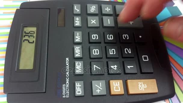 Mans fingers using a large button calculator
