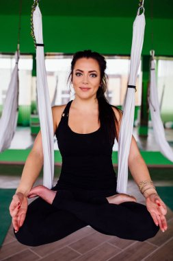 portrait young women making antigravity yoga in the lotus position. Aerial aero fly fitness. white hammocks.