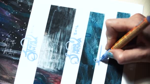 Girl artist signs some of his works. Painted sign of a master. Signature print on a blue felt-tip marker