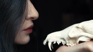 Mysterious young witch whispers a curse and spell holding a skull in the hands of a fox.