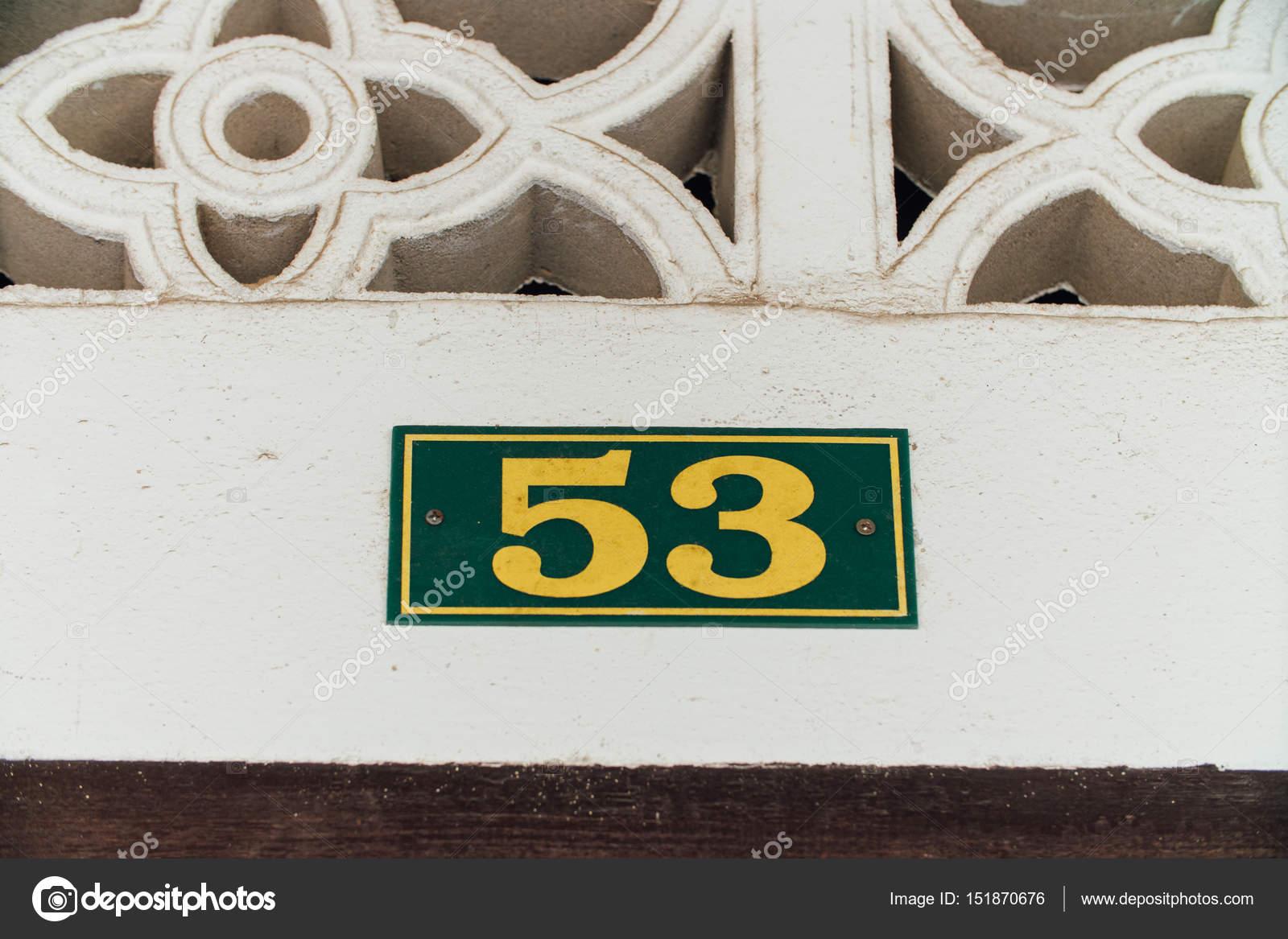 Casa número 53, amarillo. Placa con marco de tornillos ...