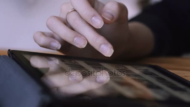 Business Girl flips through a photo album on a tablet. The students hand slides on the tablets