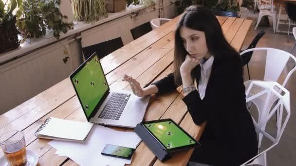Üzletasszony, tábla-PC használata zöld érintőképernyő kávézóban a fa asztal