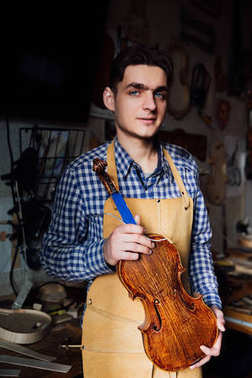 portrait of a young luthier with a handcrafted violin in his workshop with the tools.