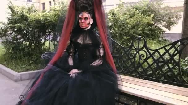 Halloween-Mädchen in Hexenuniform auf einer Bank im Stadtwald. Rätsel und Horror-Konzept.