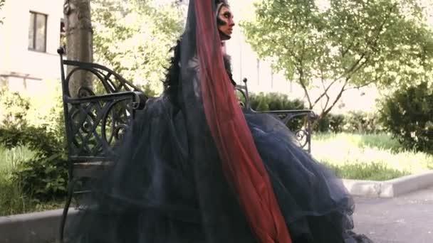 Halloween Mädchen in der Hexe sitzen auf einer Bank im Park Stadtwald. Mystery und Horror-Konzept.