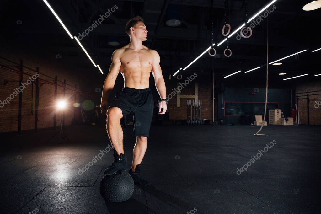 Confident muscled man doing push up from MEDICINE ball in gym.