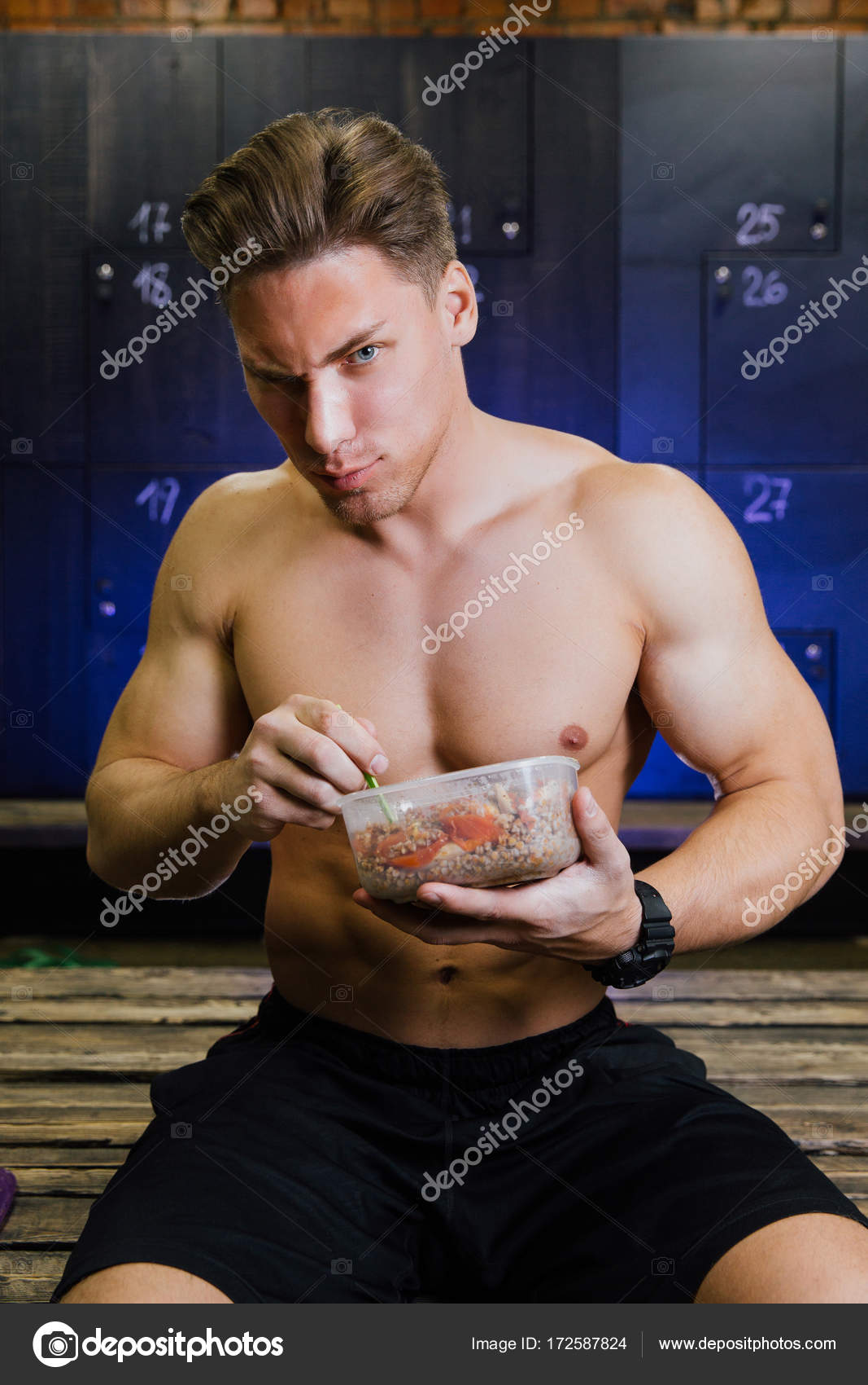 Fitness model of a bodybuilder guy eating food from a plastic ...