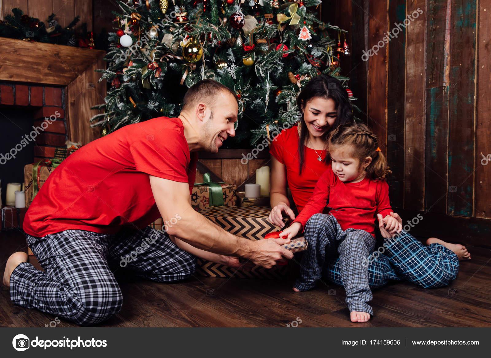 Familia En Pijamas Juegos Junto A Un Arbol De Navidad Y Una Chimenea